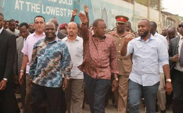 President Uhuru Kenyatta walks with Mombasa Governor Hassan Joho (right) and Nyali MP Hezron Awiti (left) on Wednesday after officially opening a new wing of the Kongowea Market.