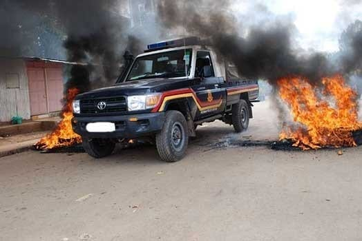 A police vehicle is driven fast between burning tyres in a past incident. PHOTO   FILE