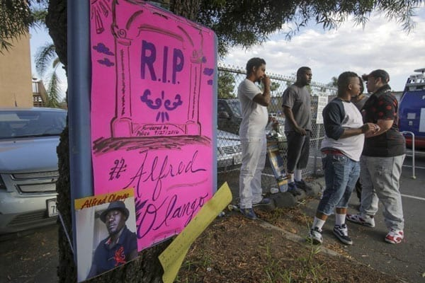 Demonstrators stand near a poster during a rally in El Cajon, a suburb of San Diego, California on September 28, 2016, in protest of the police shooting the night before. PHOTO | BILL WECHTER | NATION MEDIA GROUP