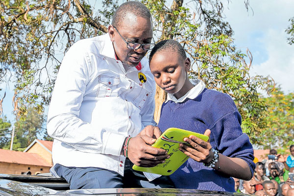 President Uhuru Kenyatta looks on as Naomi, a pupil of Makutano Primary School in West Pokot County, demonstrates how a Digital Learning Programme tablet works. PHOTO   PSCU