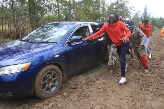 Olympics women's 800m bronze medalist Margaret Nyairera (in red jacket) is assisted by villagers of Mureru in Kieni to push a car she was riding in to the homecoming party of Olympic 400m hurdles silver medalist Boniface Mucheru. PHOTO | JOSEPH KANYI