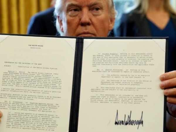 US President Donald Trump holds up a signed executive order to advance construction of the Dakota Access pipeline at the White House in Washington January 24, 2017. /REUTERS