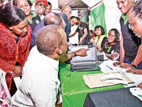 President Uhuru Kenyatta confirms his bio-data at a polling station during the voter registration drive in Kitui county./ PSCU