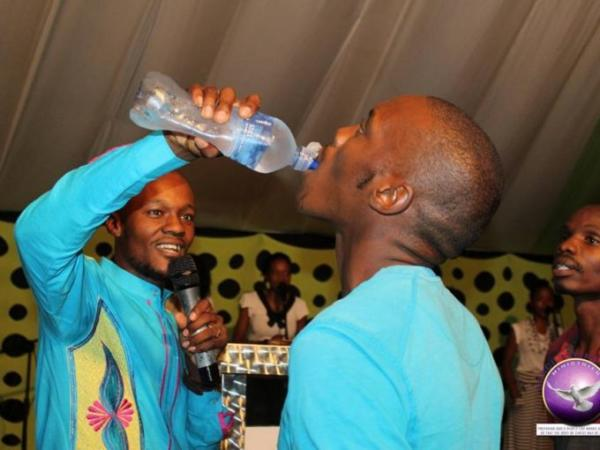 Pastor Light Monyeki feeding a congregant the mixture of water and 'Rattex'. /THE TIMES
