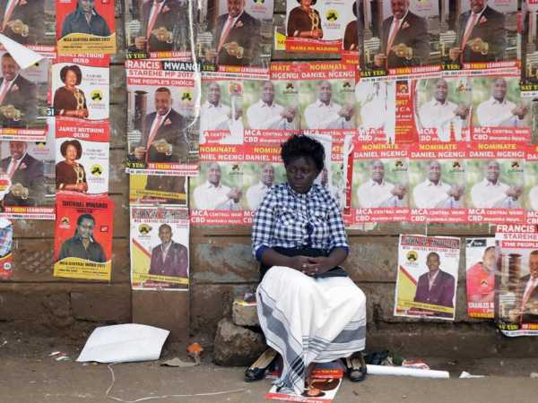 A woman sits in front of campaign posters as she waits to cast her ballot, during the Jubilee Party primary elections, at a polling centre in Nairobi, Kenya April 26, 2017. REUTERS/Thomas Mukoya